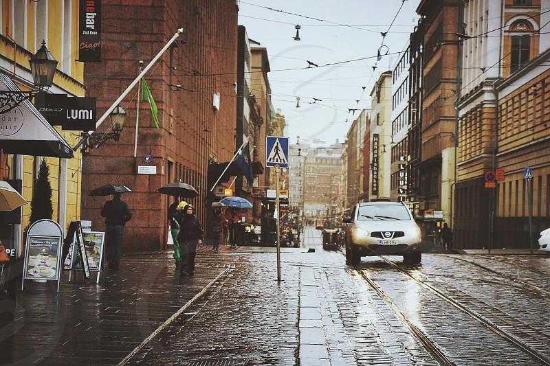 FIGURES HOLDING BLACK UMBRELLAS WALKING DOWN STONE ROAD NEAR BUIDLINGS photo