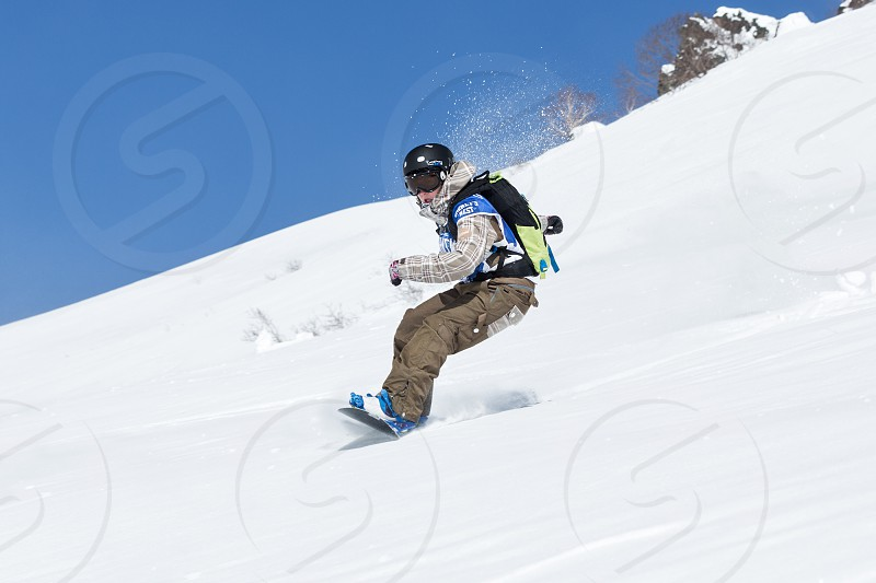 """KAMCHATKA RUSSIA - MARCH 9 2014: Girl snowboarder rides steep mountains. Competitions freeride skiers and snowboarders """"Kamchatka Freeride Open Cup"""". Russia Far East Kamchatka Peninsula. photo"""