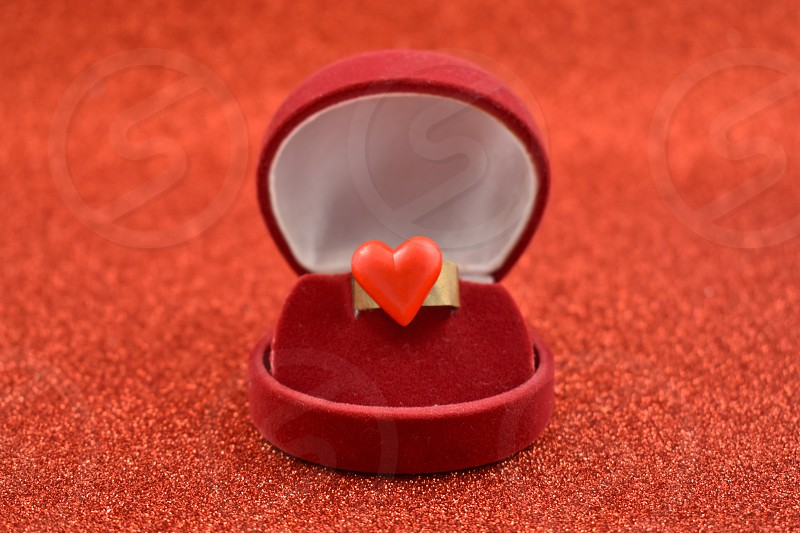 Ring with red heart. Ring in gift box. Propose day concept. Ring of love on a red background photo