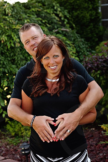 man hugging a woman with brown curly hair photo