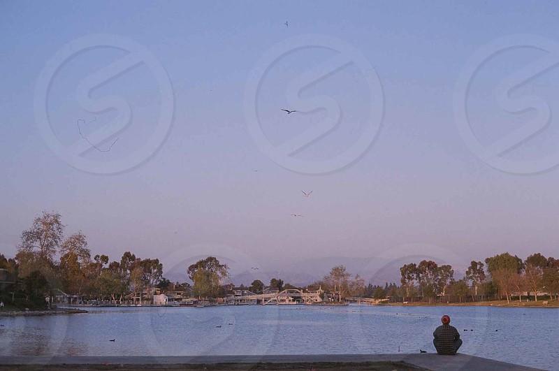 man sitting on a lake photo