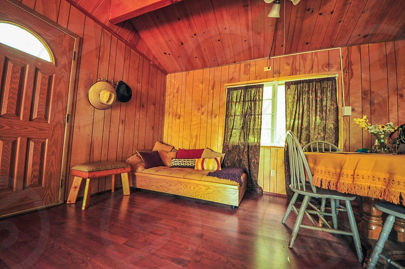 cabin home comfort interior interior design wood wooden cabin lounging dining area relaxation cozy lifestyle chairs window sunshine decor design rental vacation trip getaway mountains nature walls pillows hats curtains simplicity  photo
