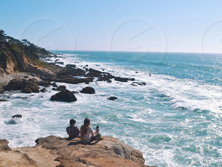 man and woman sitting on rock hill on sea side under clear blue sky photo