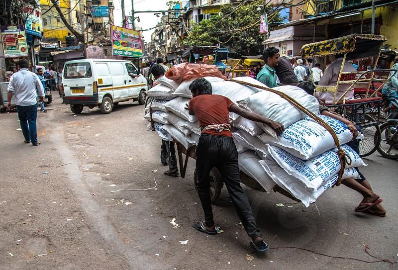 men pushing cart loaded with sacks photo