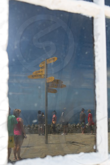 A directional sign reflected in the glass of a window photo