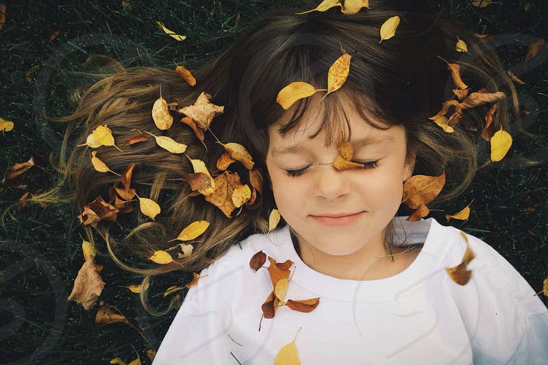 Young girl laying in the leaves  photo