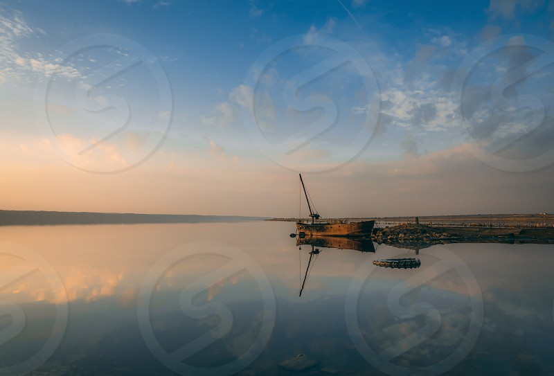 Panoramic view of the lake and the old boat at sunset of a summer day photo