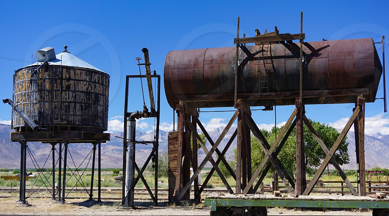 Historic steam railroad tanks for water and fuel beside tracks in an old narrow gauge line railway yard in Laws California in the Owens Valley the Sierra Nevada mountains behind them. photo