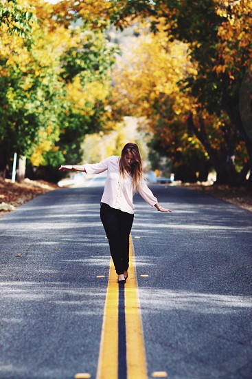 Girl walking in the middle of road.  photo