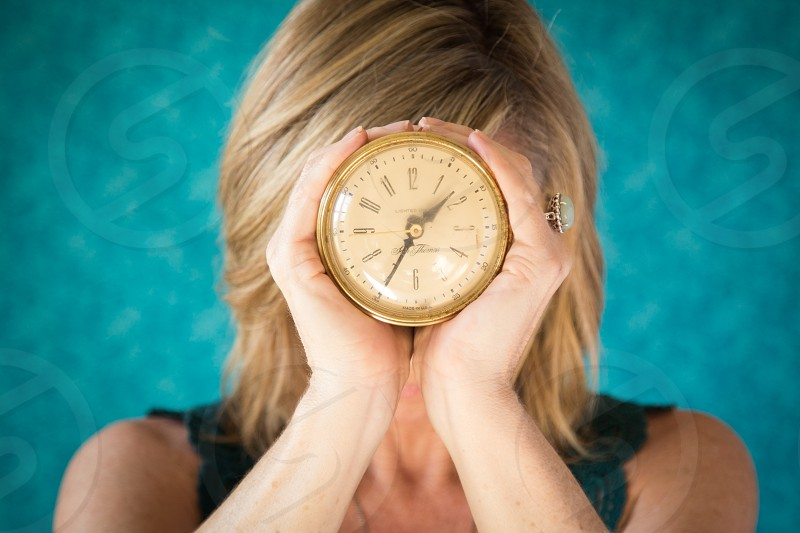 Woman holding a clock in front of her face. photo
