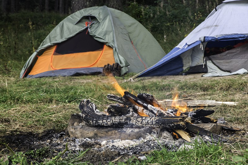 Two tents in forest. Fire on foreground photo