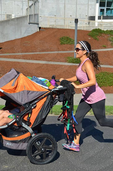 Woman running pushing her double stroller photo