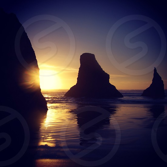 rock formation by the beach with orange sunset photo