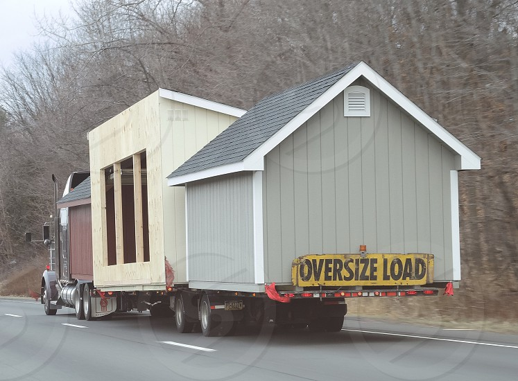 Tractor Trailer Hauling Mini House on Street photo