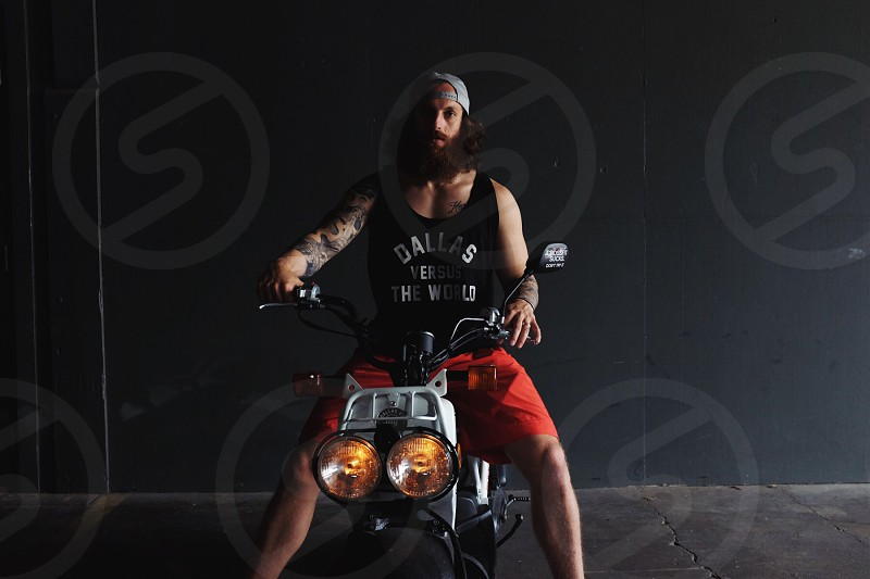 man in black tank top riding gray and black motorcycke photo