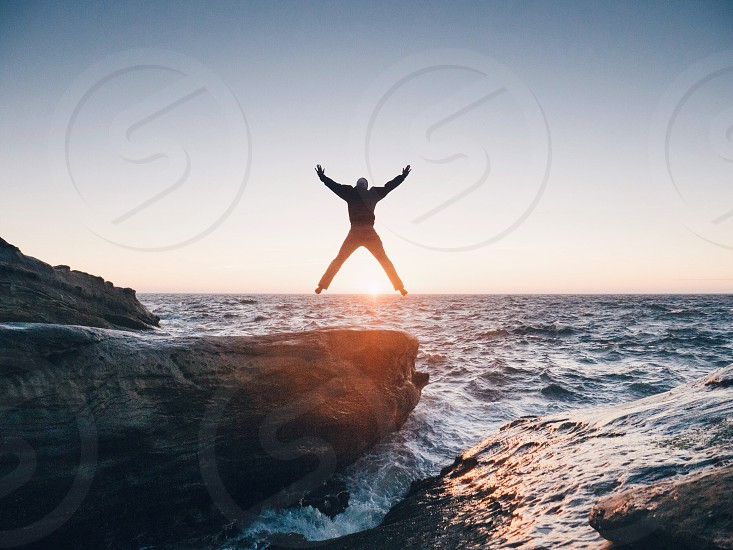 man jumped on the rock by the sea photo