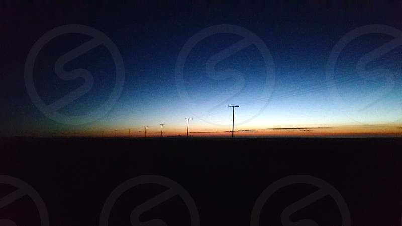 Sunrise on the highway silhouetting power poles. photo