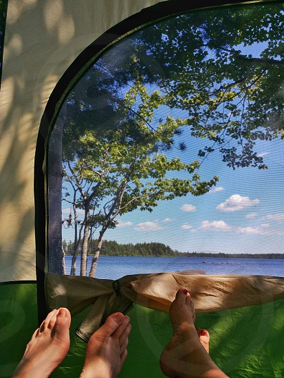 The view from inside the tent looking out through the door. A view of the lake. Tent landscape view lake blue water island summer birch trees camping reasons for travel Nova Scotia Canada feet photo