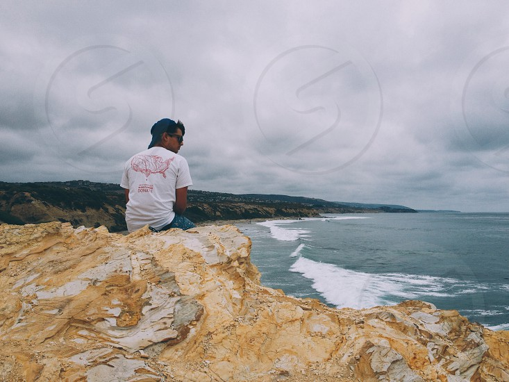 man sitting on rock facing ocean view photography photo