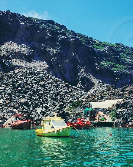 Boat water ocean sea yellow mountain volcano volcanic rock Greece vacation photo