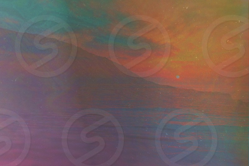 brown blue red orange green artwork of sun over water by mountain photo