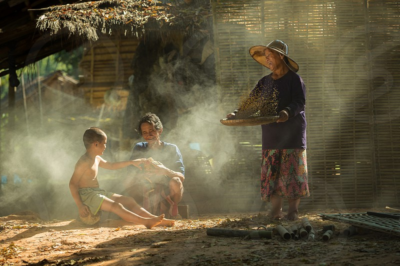 Thai family Rural Thailand's northeast. A simple and happy lifestyle. They are enjoying their pet chickens. photo