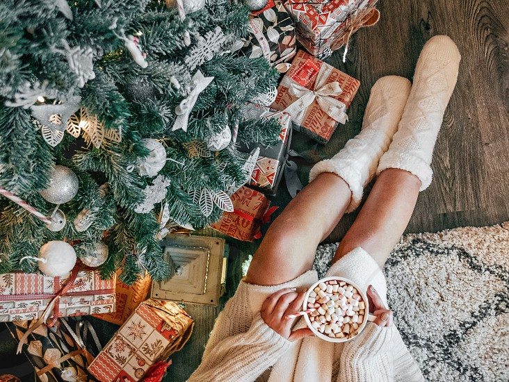 Woman in warm and cozy winter socks sitting by the christmas tree and drinking hot cocoa. photo