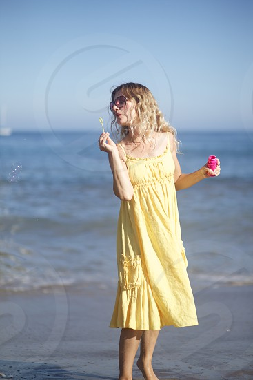 woman in yellow spaghetti strap dress on beach blowing bubble toy during daytime photo