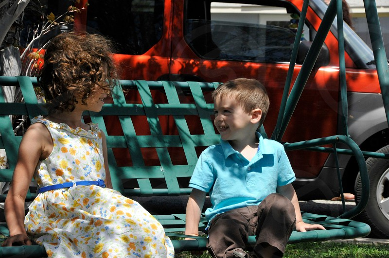 boy in blue polo shirt and gray pants sitting on bench with the girl in yellow floral printed and white dress photo