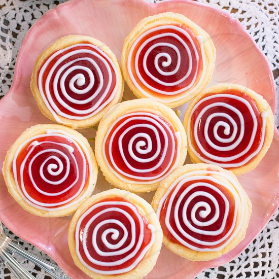 Strawberry cheesecake tartlets with spiral swirl white frosting on a pink place and lace tablecloth. dessert food pastries party photo
