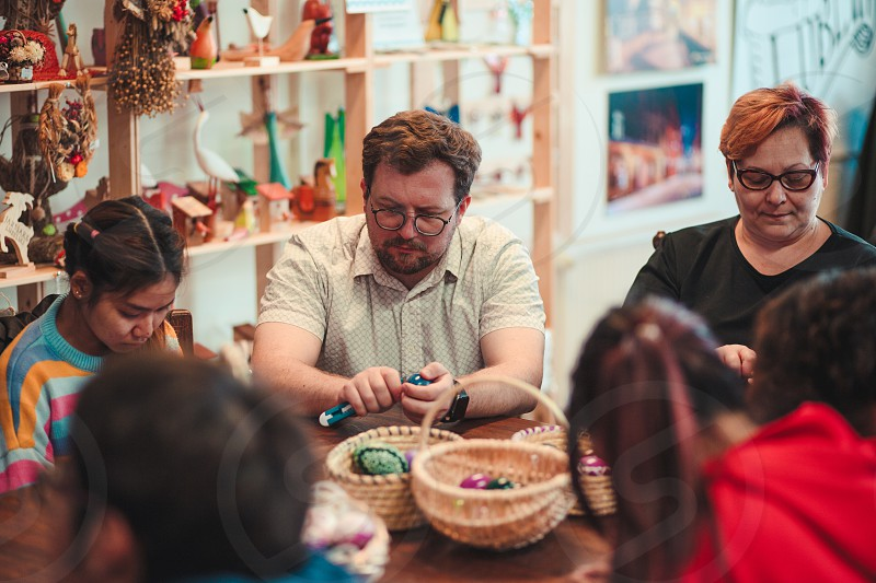 People decorating the Easter eggs by scratching patterns on dyed eggs. Traditional Easter time spring time new beginnings. Candid people real moments authentic situations photo