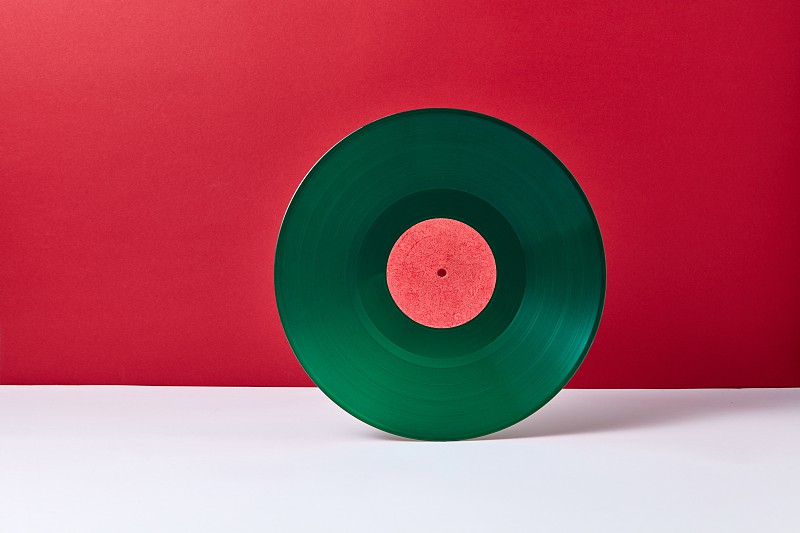 A round music green vinyl record on a duotone red gray background. Retro audio technology. Place for text. photo