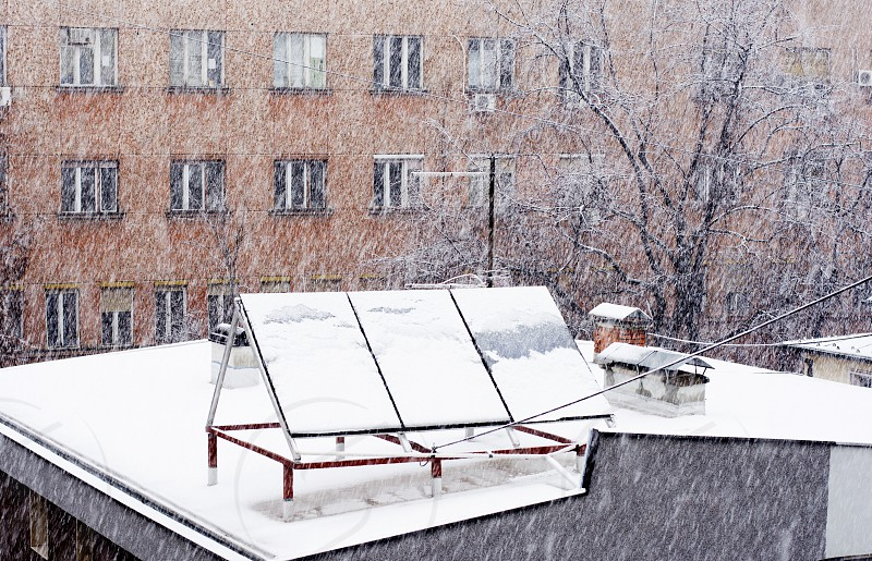 Solar panels on the roof of a modern house in city center at winter time while snowing. photo