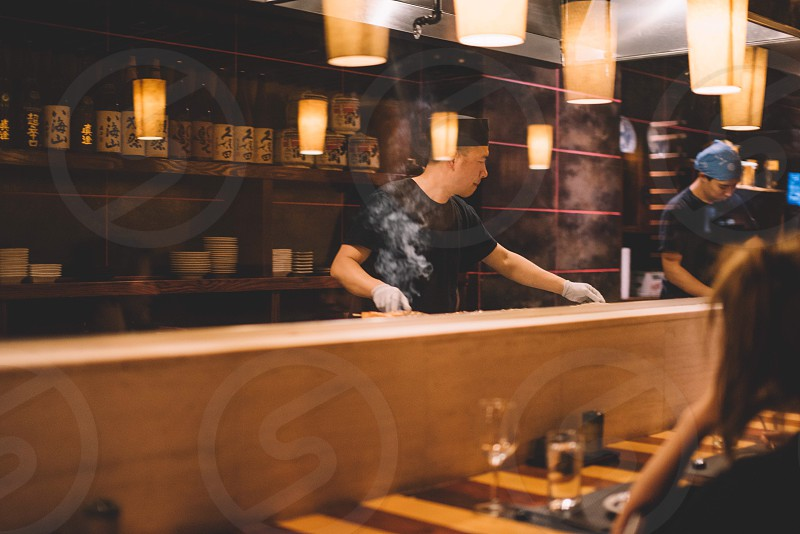 focus photography of man wearing crew neck black shirt cooking in a japanese restaurant photo