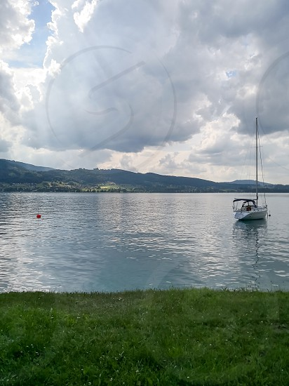 a calm view of an austrian lake by the road photo
