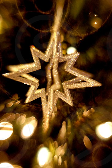 Silver star holiday ornament on a Christmas tree photo