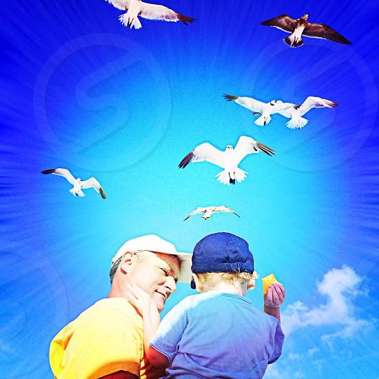 man holding a boy feeding birds photo