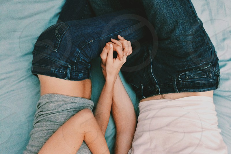 man and woman in a denim lying leg to leg on a bed photo