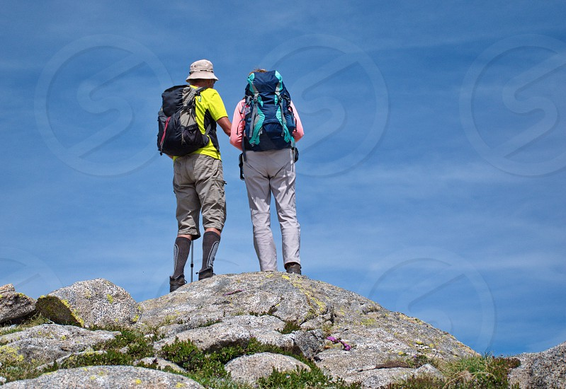 Low angle view of senior couple hiking in Dolomites photo