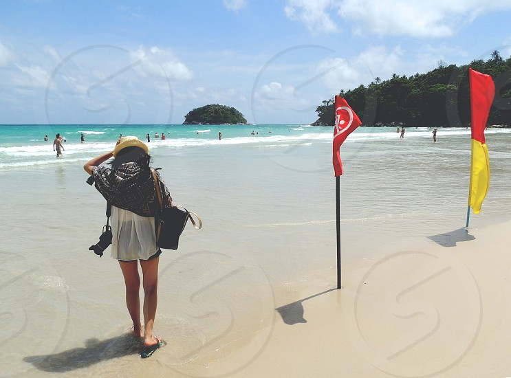 woman wearing white top and black short shorts with beige sun hat carrying black bag and black DSLR camera walking on seashore at daytime photo