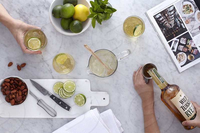 person holding white brown glass bottle pouring in cup beside slice lemons on white cutting board  on white table photo