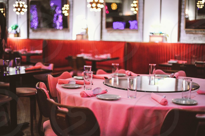 interior restaurant view with a pink linen covered round set table with red booths in the distance photo