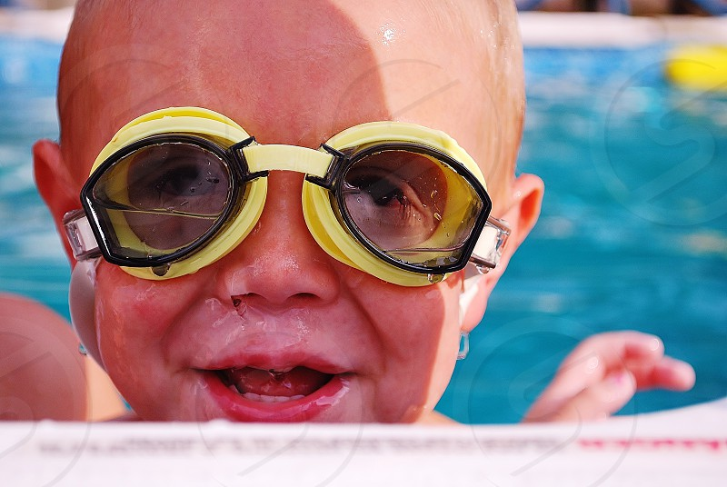Boy swimming in pool with goggles photo