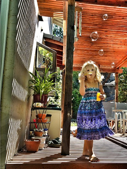 girl in blue dress blowing bubbles photo