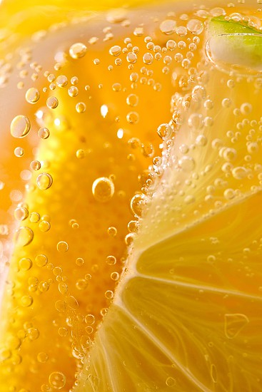 Juicy slices of ripe lemon with bubbles in a glass of water. Macro photo of refreshing lemonade photo