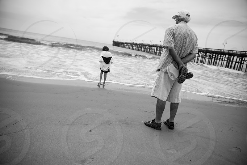 a grandfather watches his grandson enjoy the waves at the beach photo
