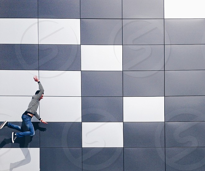 man with black hair in gray long sleeved shirt and blue denim jeans jumped near white and black wall photo