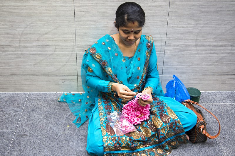 Indian woman in national clothes weaves a garland of flowers for the decoration of the temple photo