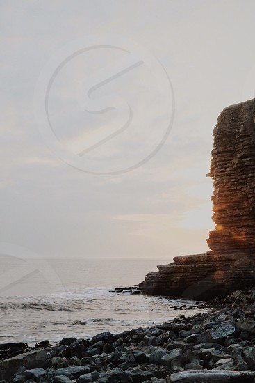 sea waves raging towards stone formation during golden hour photo