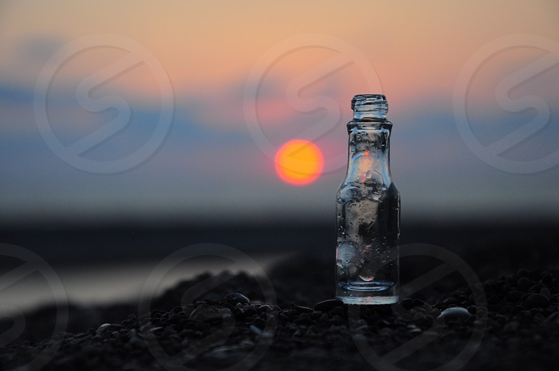 clear glass bottle on brown sand photo